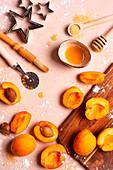 Backstilleben mit Aprikosen, Honig, braunem Zucker und Utensilien