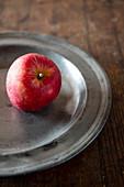 Ein roter Apfel auf Zinnteller