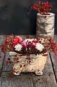 Gesteck aus Hagebutten und Strohblumen
