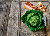 Savoy cabbage, bacon and onions on a wooden background