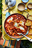 Camping-Frühstück mit Baked Beans, Würstchen und Spiegelei