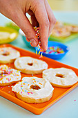 Apfeldoughnuts mit Zuckerstreuseln bestreuen