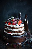 Rustic layered cocoa cake with cream and strawberries blueberries cherries