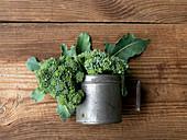 Frischer Broccoli in Metallgefäß auf Holzuntergrund