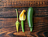 Fresh green zucchini and zucchini flowers on a wooden background