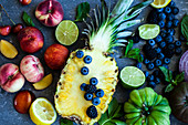 Rainbow of fruit, vegetables and herbs on a blue surface