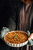 Woman serving apple oat crumble