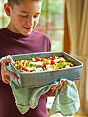 Junge hält Backform mit vegetarischem Halloumi-Auflauf