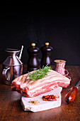 Piece of pork belly with a sprig of rosemary