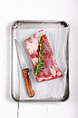 Piece of pork belly with a sprig of rosemary in an metal roasting tray