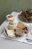 A cheese platter with honey, nuts, grapes and pumpkin cream