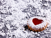 A Linz cookie surrounded by powdered sugar