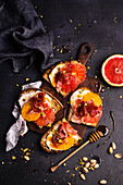 Toasts with creamy cheese, orange, grapefruit, Parma ham, honey and pistachios