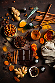 Winter spices ginger, cinnamon, star anise, turmeric, dryed apricots, raisins, hazelnuts, chocolate and caramel