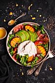 Salat mit Rucola, Pfirsichen, Avocado, Burrata und Parmaschinken
