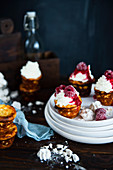 Mini cheesecakes with whipped cream, raspberry sauce and frozen raspberries