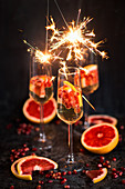 New Years Eve champagne in glasses with grapefruits, pomegranate seeds and sparklers