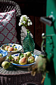 Fresh pears and glass vase of wildflowers on wicker table
