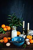 Weihnachtliche Backzutaten - blaue Schüssel, Clementinen und Milch