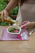 Malvenbreiumschlag zubereiten: Malvenblätter und Malvenblüten mit Olivenöl angiessen