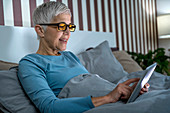 Mature woman wearing blue light blocking glasses
