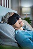 Mature woman wearing black sleep mask
