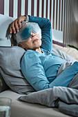 Mature woman wearing cooling eye mask