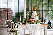 Two celebration cakes on set country-house table in industrial building