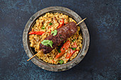 Traditional Middle Eastern meat Kebab with rice in rustic metal plate