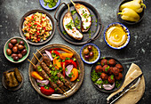 Middle eastern dinner with grilled kebab, falafel, roasted and fresh vegetables