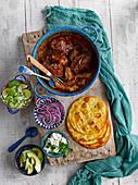 Mexikanischer Schweinefleisch-Chili-Eintopf serviert mit Tortillafladen und Beilagen
