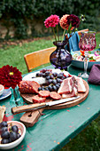 Ham, salami and grapes on charcuterie board on table outdoors