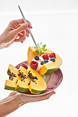 Hand carrying plate with fruit dessert and poking slices of papaya with yoghurt and berries with stick