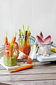 Drei Picknick-Dips (Erbsen-Guacamole, Räucherlachs, gebratene Paprika) mit Gemüsesticks im Glas