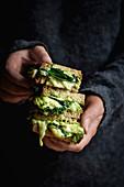 Hände halten einen Stapel gegrillte grüne Käsesandwiches