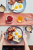 Frühstücksteller mit Pancakes, Spiegeleiern, Bacon und Käse