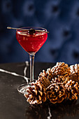 Shiny glass of red alcohol drink garnished with cherry in bar