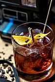 Cocktail mit Orangenschale, Eiswürfeln und Kaffeebohnen in einer Bar