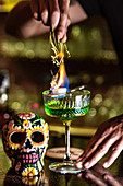 Unrecognizable crop barman standing at counter in bar and burning green alcohol drink