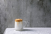 Dalgona frothy coffee (trend korean drink) - milk latte with coffee foam in glass mug