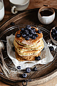 Ein Stapel Pancakes mit Blaubeeren auf Holztablett
