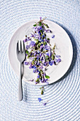 Violet purple edible flowers on white plate with dessert fork over blue knitted background