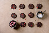 Homemade dark chocolate salted brownies cookies decorated by dried raspberries, served with salt flakes, frozen berries