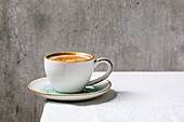 Black coffee espresso with foam in white ceramic cup with saucer standing on white cotton table cloth