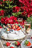 Pavlova with cream and fresh fruit served in the garden with champagne