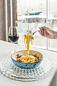 Holding spoon with pasta while enjoying meal with red wine at home