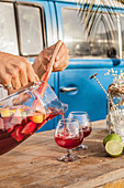 Pouring cool sangria in crystal glasses on wooden table against blue van on tropical beach