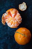 Eine ganze und eine geschälte Mandarine auf blauem Untergrund