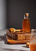 Honig in Glasfläschchen und auf Honiglöffel