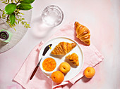 Summer breakfast scene with croissants, apricots and jam